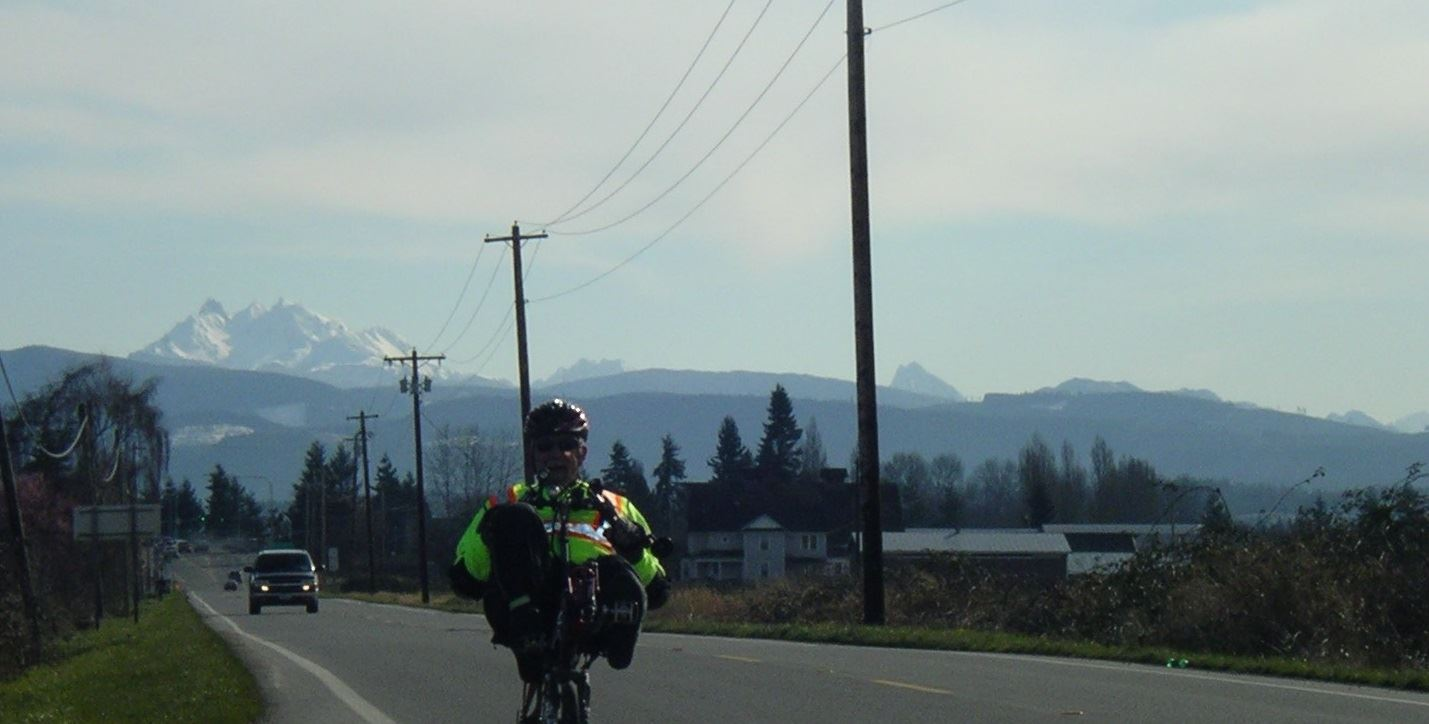 Recumbent rider with Cascade mountains in the background